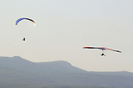 Ellenville, NY - A hang gliders and a paraglider soar in the sky above Ellenville with the Catskill Mountains in the background on May 30, 2009.
