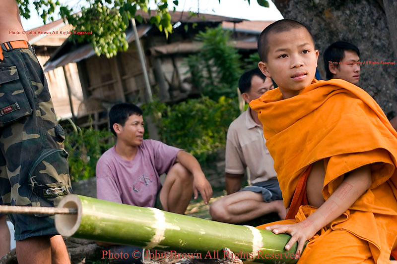 A young Buddhist monk is sitting on a bamboo rocket at a temple in Muang Sing, Northern Laos.