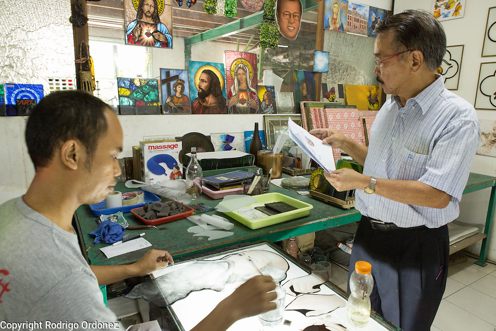 Eztu Glass founder and CEO Brian Yaputra (right) examines a stained glass window design at his company's factory in Tangerang, near Jakarta, Indonesia, on July 2, 2015.