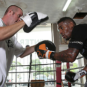 """WINTER HAVEN, FL - MAY 05: Boxer Willie Monroe Jr. (R) hits the mitts with trainer Tony Morgan at the Winter Haven Boxing Gym on May 5, 2015 in Winter Haven, Florida. Monroe will challenge middleweight world champion Gennady """"GGG"""" Golovkin for the WBA world championship title in Los Angeles on May 16.  (Photo by Alex Menendez/Getty Images) *** Local Caption *** Willie Monroe Jr.; Tony Morgan"""