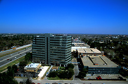 Aerial view of business complex next to freeway.