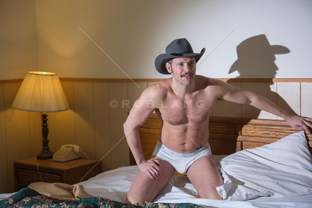 sexy cowboy in briefs kneeling in bed in a motel room