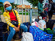 05 JULY 2017 - POIPET, CAMBODIA: A Cambodian migrant worker going to Thailand waits with her luggage for a labor broker to provide her paperwork. Cambodian migrant workers in Poipet headed for Thailand take a tuk-tuk (three wheeled taxi) to the Thai-Cambodian border. The Thai government proposed new rules for foreign workers recently. The new rules include fines of between 400,000 and 800,00 Thai Baht ($12,000 - $24,000 US) and jail sentences of up to five years for illegal workers and people who hire illegal workers. Hundreds of companies fired their Cambodian and Burmese workers and tens of thousands of workers left Thailand to return to their countries of origin. Employers and human rights activists complained about the severity of the punishment and sudden implementation of the rules. On Tuesday, 4 July, the Thai government suspended the new rules for 180 days and the Cambodian and Myanmar governments urged their citizens to stay in Thailand, but the exodus of workers continued through Wednesday.     PHOTO BY JACK KURTZ