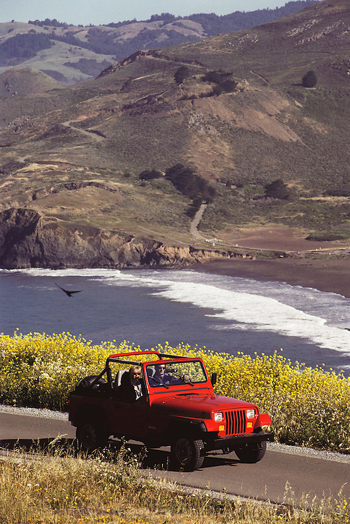 Red Jeep on northern California coast road in Marin County. MODEL RELEASED.