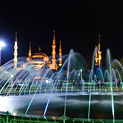 Illuminated fountain in Sultanahment Park with the Blue Mosque in the background. Sultan Ahmed Mosque (Turkish: Sultanahmet Camii) known popularly as the Blue Mosque is a Muslim (Sunni) Mosque in the center of Istanbul's old town district of Sultanahmet. It was commissioned by Sultan Ahmed I and completed in 1616,
