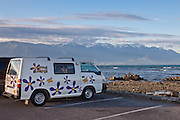 "A tourist van named the ""Hippie Camper"" at Kaikoura, with the Seaward Range in the distance, New Zealand."