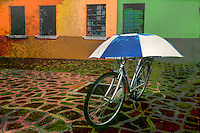 Blue and white umbrella protects bike parked on Burano Island near Venice, Italy