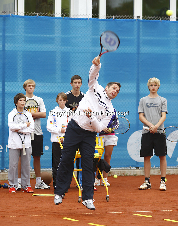 Internatschueler in der BTV TennisBase in Oberhaching / Muenchen,.Trainer Sascha Petratscheck demonstriert einen Aufschlag,Gruppe junger Spieler dahinter schaut zu,Aktion,Training, Hochformat,Ganzkoerper,.Kinder,Jugendliche,Nachwuchsspieler,