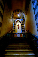 """""""Climb to Christ - St. Andrew Cathedral of Amalfi""""… <br /> <br /> On the last of three glorious days in Positano, I arose early to catch sunrise over the village. However, at about 10:00 am …the cold rains came down dampening the glorious sun. I caught the rain soaked ferry down the coast to the seaside town of Amalfi. The Cattedrale di Sant'Andrea/Duomo di Amalfi is usually packed with tourists bused and ferried from hundreds of miles away, but with the dreary weather, many chose to stay away. There has been a church on this site in Amalfi since 596 AD and the one built in the 9th century still stands today. The present cathedral was built adjacent to the old one in the early 13th century to provide a suitable resting place for St. Andrew the Apostle. The two were originally joined together to form a single, six-nave Romanesque cathedral. Stairs near the east end descend into the Crypt of St. Andrew, where the saint's relics are kept in the central altar. The crypt is decorated with beautiful Baroque murals from 1660. Upon leaving the crypt, I turned to ascend the stairs and with little window light because of the rain, a single light illuminated the crucifix stopping me in my tracks. Others behind me also paused as I quickly took out my camera to capture this dramatic image. Tourists actually gathered behind me as I slowly moved up the steps taking more photos; perhaps for the first time, others took notice of this divinatory and transcendent vision."""