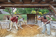Workers mixing mortar made from sand and limestone, at the Chateau de Guedelon, a castle built since 1997 using only medieval materials and processes, photographed in 2017, in Treigny, Yonne, Burgundy, France. The Guedelon project was begun in 1997 by Michel Guyot, owner of the nearby Chateau de Saint-Fargeau, with architect Jacques Moulin. It is an educational and scientific project with the aim of understanding medieval building techniques and the chateau should be completed in the 2020s. Picture by Manuel Cohen