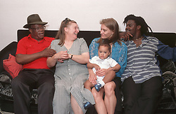 Multiracial family group with three generations sitting on sofa laughing,