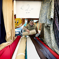 Nederland, Amsterdam , 20 oktober 2010..De kleding en stoffen afdeling van de markt op Plein 40-45.A market trader between his fabrics on the market on Plein 40-45 in Amsterdam.