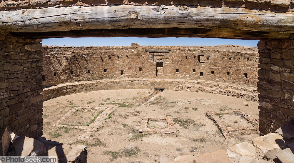 Casa Rinconada, occupied about AD 1140-1200, is an isolated great kiva (out of four in Chaco Canyon), built 63 feet (19 m) in diameter with a circular inner bench, masonry firebox, masonry vaults, 34 niches, four large pits for seating roof supports, plus an unusual 39-foot (12 m) passage dug underground through sandstone and shale. Chaco Culture National Historical Park hosts the densest and most exceptional concentration of pueblos in the American Southwest and is a UNESCO World Heritage Site. Chaco Canyon is in remote northwestern New Mexico, between Albuquerque and Farmington, USA. From 850 AD to 1250 AD, Chaco Canyon advanced then declined as a major center of culture for the Ancient Pueblo Peoples. Chacoans quarried sandstone blocks and hauled timber from great distances, assembling fifteen major complexes that remained the largest buildings in North America until the 1800s. Climate change may have led to its abandonment, beginning with a 50-year drought starting in 1130. This panorama was stitched from 2 overlapping photos.