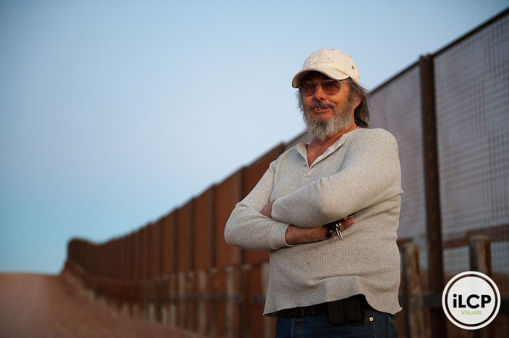 Local landowner poses near the border wall at the south edge of his property.