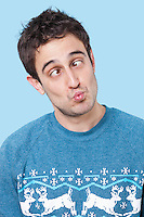Young man making funny faces over blue background