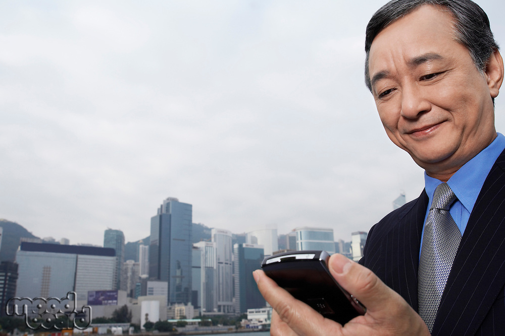 Middle-aged business man using PDA office buildings in background