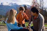 A family plays at Meadow park in Whistler on a sunny autumn day,