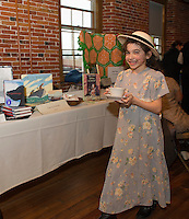 """Ilyana-Joy Gonzalez is ready for """"tea time"""" with author Terry Farish at the Lakes Region Community Services sponsored Children's Authors Tea at the Belknap Mill Tuesday evening.   (Karen Bobotas/for the Laconia Daily Sun)"""