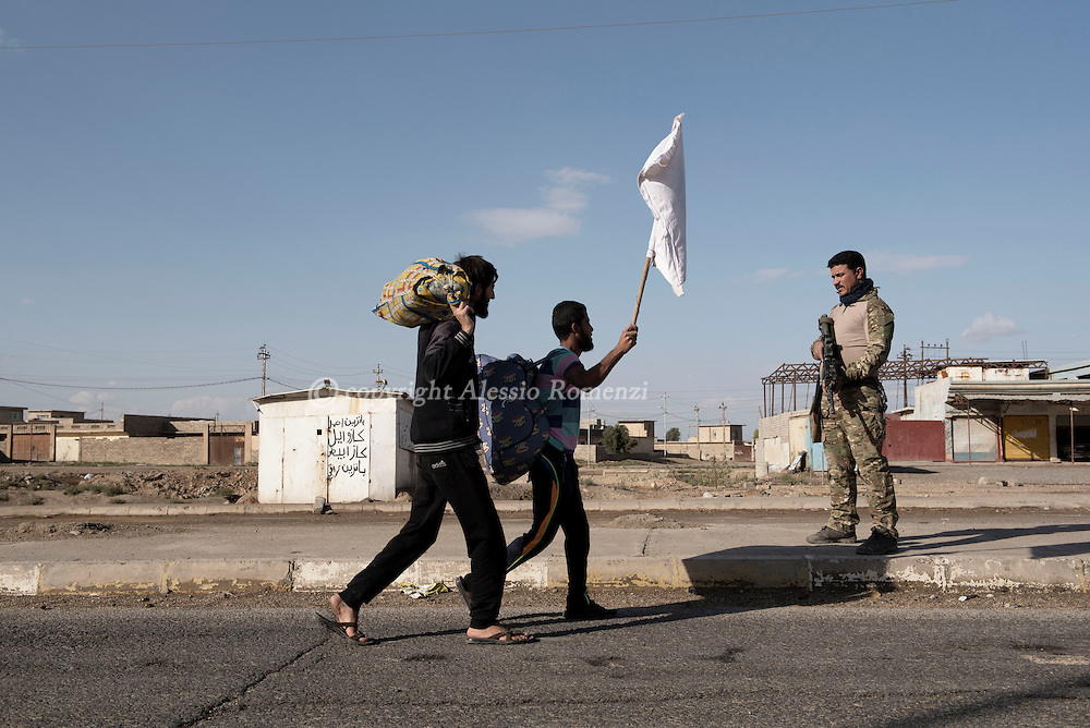 Iraq, Gogjali: Iraqi civilians, who fled the fight against jihadists of the Islamic State group in the city of Mosul, walk in front of a special forces Iraqi soldier, as they head to camps housing displaced people on November 2, 2016. Alessio Romenzi