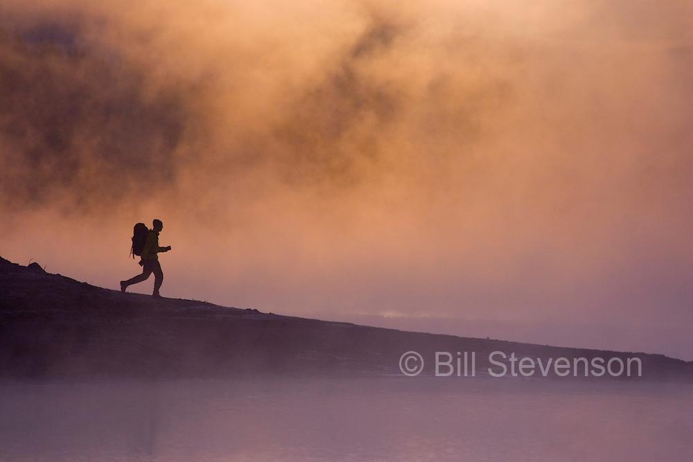 A photo of a man hiking along the shore of a foggy lake at sunrise near Truckee, CA.