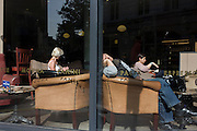 Three woman in the warm sunshine in a window of Caffe Nero in central London.