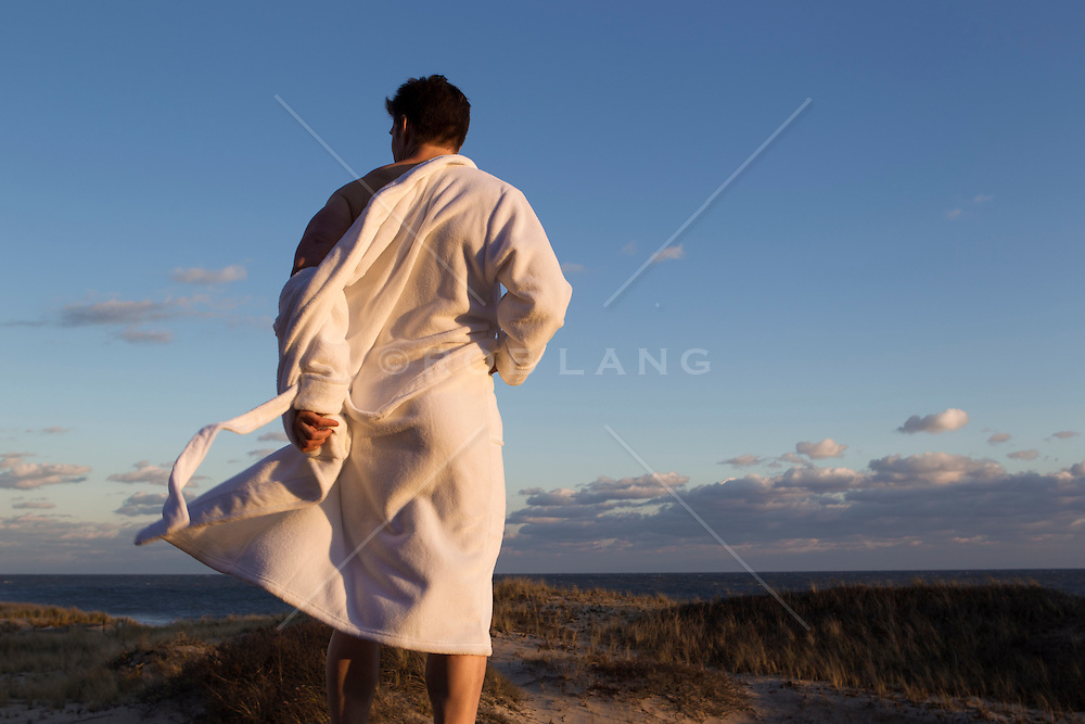 man taking off his white robe at the ocean in Amagansett, NY