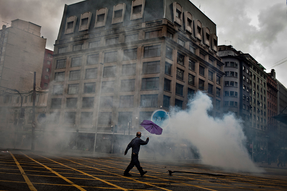 A man tries to cross Santiago´s main street after the police threw tear gas during a students protest, Santiago, Chile. August 23, 2012. Photo/Tomas Munita