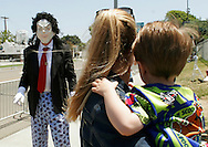A mother and child watch a figure wearing a Michael Jackson mask outside the court in Santa Maria, California where the Jackson trial is taking place June 2, 2005.  Closing arguments began in the Jackson sex abuse trial, the final showdown between prosecutors and defense lawyers in a bitter, four-month court fight that could end in prison for one of the world's best-known entertainers.