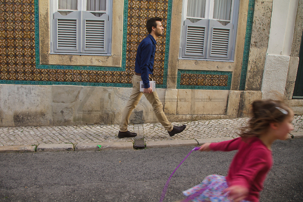 Man and girl passing by a house with facade decorated with ceramic tiles at Madragoa district in Lisboa.