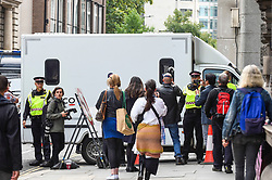 © Licensed to London News Pictures. 07/09/2020. LONDON, UK.  Photographers follow one of two police vans entering the Old Bailey.  Supporters of Wikileaks founder Julian Assange stage a protest outside the Old Bailey as his extradition hearing, which is expected to last for the next three or four weeks, resumes after it was postponed due to the coronavirus pandemic lockdown.  Julian Assange is wanted in the US for allegedly conspiring with army intelligence analyst Chelsea Manning to expose military secrets in 2010.  Photo credit: Stephen Chung/LNP