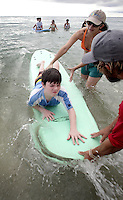 Autistic cilds attend the surf lessons at Boynton Beach Oceanfront Park's beach on October 20, 2013. The City of Boynton Beach Recreation Department is partnering with HULA Surf and Paddle School to provide free surf lessons for Palm Beach County School for Autism. More than 40 local surfers and volunteers will assist the children, for all ages, in half-hour increments in the water.  Photo Cristobal Herrera