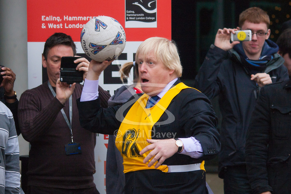 Ealing, London, December 9th 2014. Mayor of London Boris Johnson visits Ealing, Hammersmith and Fulham College accompanied by   Deputy Mayor for Policing and Crime Stephen Greenhlagh to launch a new initiative to increase black and ethnic minority applicants to the Met. PICTURED: Boris Johnson prepares to shoot during a game of netball with college students.