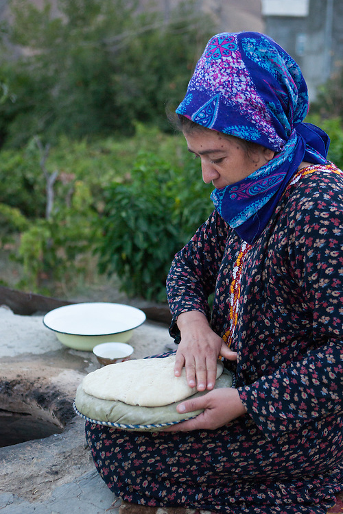 A woman lays dough on an oven mitt before placing it in the outdoor stone oven, early in the morning, Turkmenistan
