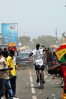 Ghana, Accra, 2007. A celebrating biker gives irreverent chase to the presidential motorcade on Independence Day.