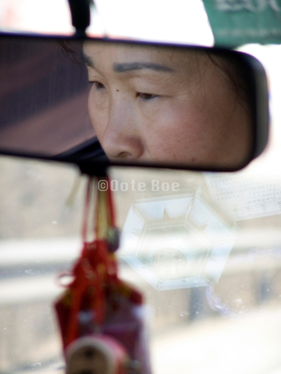 eyes of an Asian woman seen in the rearview mirror China eyes in focus