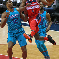 Washington Wizards guard John Wall (2) makes a pass under the basket against Charlotte Hornets center Dwight Howard (12) in the first half at Capital One Arena in Washington, D.C. on March 31, 2018.  Photo by Mark Goldman/UPI