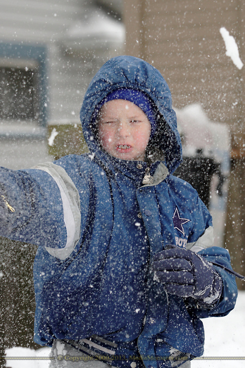 Keigen Richardson, 8, of Dayton finds out what happens when you smash a block of ice-topped snow with his fist:  the pieces go everywhere, including his face.
