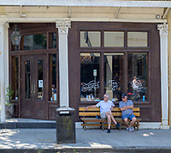 New Orleans, LA, USA -- May 26, 2019. Two men sit on a bench and relax outside a restaurant in New Orleans.