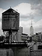 Every rooftop in Manhattan has a water tower to regulate water pressure in buildings. Empire State Building in the background.
