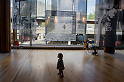A young child beneath  large screen images showing childhood of a bygone era in Britain's history, on display at London's Royalk Festival Hall on the Southbank.