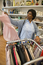 Woman looking at clothes in a charity shop,