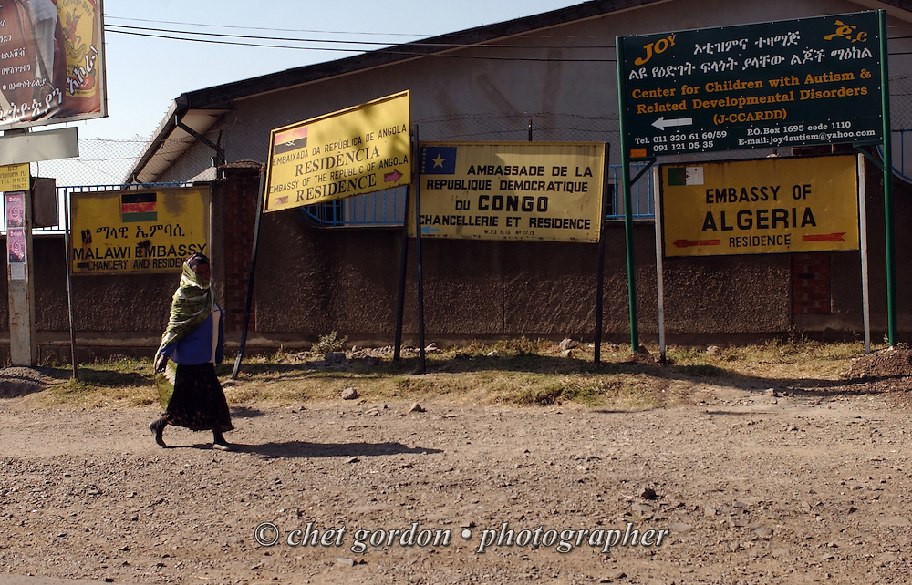 Ethiopian woman walks past signs pointing to embassy row in Addis Ababa, Ethiopia on December 6, 2005.