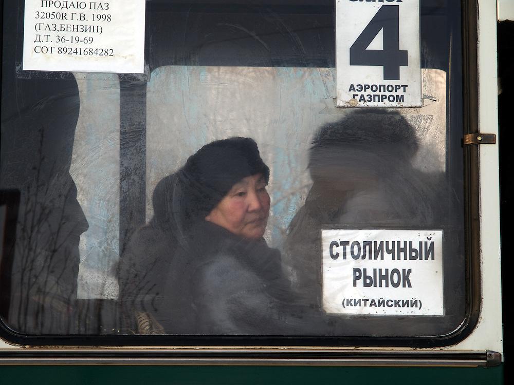 Frau hinter einer gefrorenen Autobus Glasscheibe. Jakutsk hat 236.000 Einwohner (2005) und ist Hauptstadt der Teilrepublik Sacha (auch Jakutien genannt) im Foederationskreis Russisch-Fernost und liegt am Fluss Lena. Jakutsk ist im Winter eine der kaeltesten Grossstaedte weltweit mit durchschnittlichen Winter Temperaturen von -40.9 Grad Celsius. Die Stadt ist nicht weit entfernt von Oimjakon, dem Kaeltepol der bewohnten Gebiete der Erde.<br /> <br /> Woman sitting behind a frozen window of a Yakutsk bus. Yakutsk is a city in the Russian Far East, located about 4 degrees (450 km) below the Arctic Circle. It is the capital of the Sakha (Yakutia) Republic (formerly the Yakut Autonomous Soviet Socialist Republic), Russia and a major port on the Lena River. Yakutsk is one of the coldest cities on earth, with winter temperatures averaging -40.9 degrees Celsius.