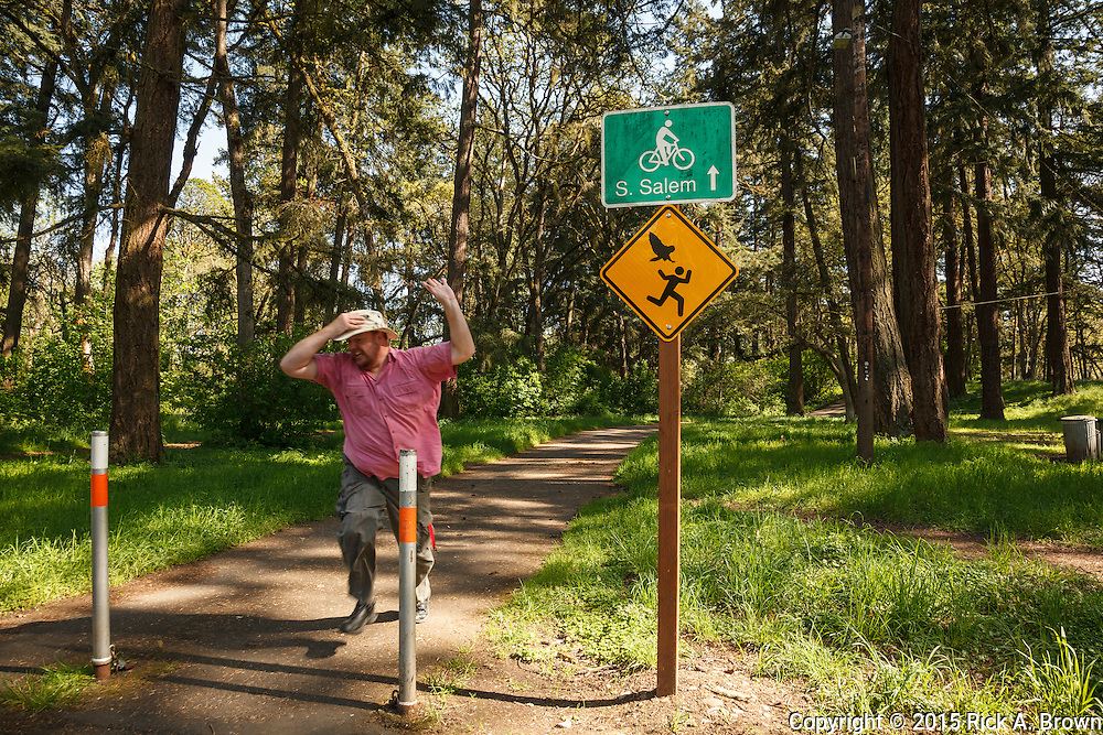 USA, Oregon, Salem, Bush Pasture Park, sign warning hikers that nesting owl may harass them and photographer making a joke about it. MR