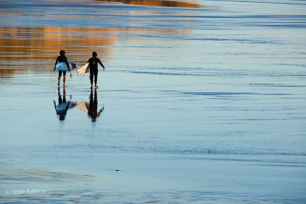 A couple of surfers head out to the surf break on Opunake beach at sunset on New Zealand's west coast  of the North Island.  The cold waters of the Tasman Sea require the use of wet suits.