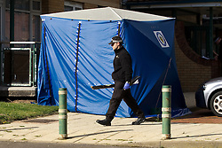 © Licensed to London News Pictures. 06/10/2012. Walsall , UK . A policeman walks in front of a blue tent erected at the scene . Police and forensic examiners investigate after two bodies were found at a block of flats . A woman was found inside a flat in Holly Court , Acacia Avenue , Walsall and a man was found dead outside the block . Photo credit : Joel Goodman/LNP