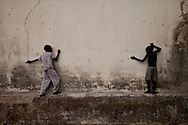 Boys play on a pockmarketed wall after an army mutiny forced many people in the town to flee across the river in Upper Nile State.