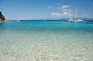 Sailing yachts off Marmari Beach on the west coast of Paxos, The Ionian Islands, The Greek Islands, Greece, Europe