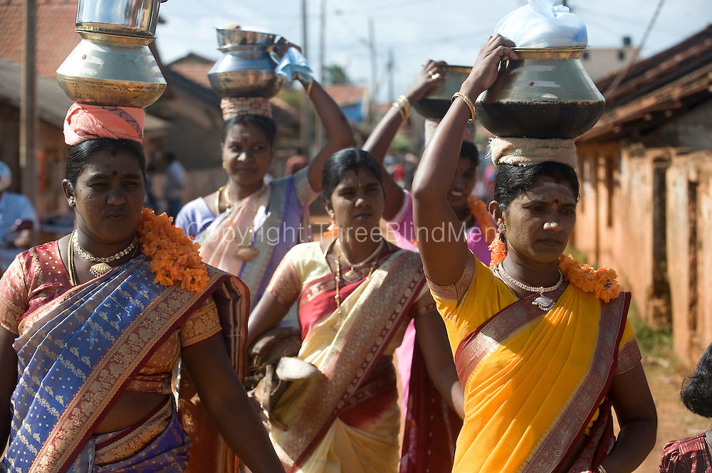 Sri Lanka. Women arrive with their cooking pots at the Kali Temple. They will cook an offering of festive food on the road in front of the temple and on the beach beside it. Festival at Kali Kovil in Udappu.