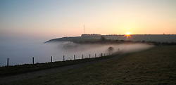 © Licensed to London News Pictures. 14/03/2014. Hampshire, UK. Fog fills the Thames Valley along Wayfarer's Way near Hannington Transmission Mast on the North Wessex Downs during sunrise this morning 14th March 2014. Photo credit : Rob Arnold/LNP